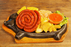 Sausage with potatoes, vegetables and hot sauce on a plate Stock Photo