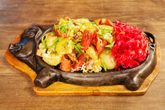 Sausage with potatoes, vegetables and hot sauce on a plate Royalty Free Stock Photos