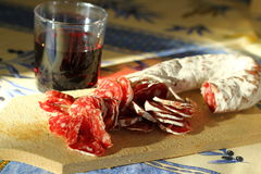 Sausage with red wine. Simple south French meal: sausage cut in thin slices and a glass of wine on the Provencal napkin Royalty Free Stock Photo
