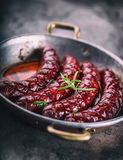 Sausage. Roasted chorizo sausage. Roasted spicy sausage chorizo home hotel or restaurant with beer vine brandy cognac whiskey. Stock Image