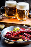 Sausage. Roasted chorizo sausage. Roasted spicy sausage chorizo home hotel or restaurant with beer vine brandy cognac whiskey. Royalty Free Stock Image