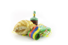 Sausage Roll with Blower and Party Popper. Small tasty sausage roll with party blower and party popper with streamers on a reflective white background Royalty Free Stock Photos