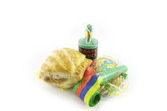Sausage Roll with Blower and Party Popper. Small tasty sausage roll with party blower and party popper with streamers on a reflective white background Stock Photos