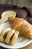Sausage roll on dish with croissant Stock Images