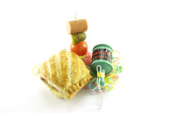 Sausage Roll and Party Popper. Small sausage roll with party popper and cocktail stick containing hot dog sausage, gherkin and tomato with streamers on a Stock Photos