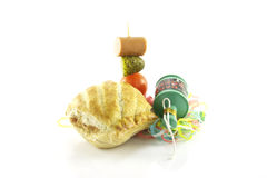 Sausage Roll and Party Popper. Small sausage roll with party popper and cocktail stick containing hot dog sausage, gherkin and tomato with streamers on a Stock Photography