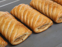 Sausage Rolls. Freshly baked sausage rolls on a non-stick oven tray Royalty Free Stock Images