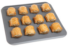 Sausage Rolls on Baking Tray. Sausage rolls fresh from the oven on a non-stick baking tray Royalty Free Stock Photography