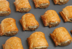 Sausage Rolls on Baking Tray. Sausage rolls straight out of the oven on a nonstick baking tray Royalty Free Stock Photos