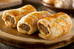 Sausage Rolls. Delicious homemade sausage rolls on a wooden serving platter Royalty Free Stock Images