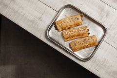 Sausage rolls in a metal baking tray. Three sausage rolls on a metal tray on a light coloured wooden table top stock images