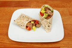 Sausage and salad wraps on a tabletop. Sausage and salad sandwich wraps on a plate on a wooden tabletop Royalty Free Stock Images