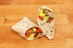 Sandwich wraps on a chopping board. Sausage and salad sandwich wraps on a wooden chopping board Royalty Free Stock Images