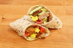 Sausage and salad wraps. Sausage and salad sandwich wraps on a wooden chopping board Royalty Free Stock Photos