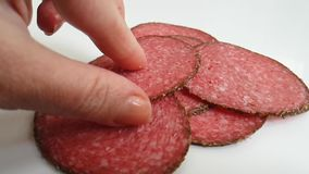 Sausage salami hands take on a white background. Slow-motion stock video footage