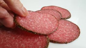 Sausage salami hands a white background. Sausage salami hands  on a white background slow-motion stock footage