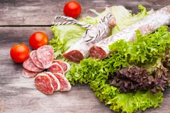 Sausage salami with noble mold and lettuce. Sausage salami with noble mold,cherry tomatoes and lettuce on the wooden table Royalty Free Stock Photos