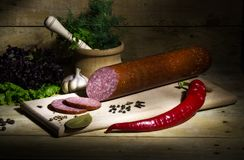 Sausage, salami, spices on a wooden table. Slices of salami isolated on a white background Royalty Free Stock Photography