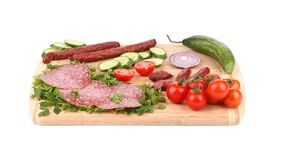 Sausage salami and vegetables on wooden platter. Royalty Free Stock Photos