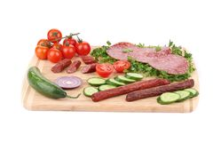 Sausage salami and vegetables on wooden platter. Stock Photos