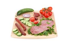 Sausage salami and vegetables on wooden platter. Royalty Free Stock Images