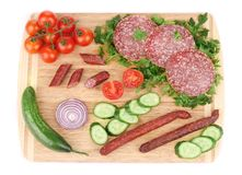 Sausage salami and vegetables on wooden platter. Royalty Free Stock Image