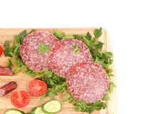 Sausage salami and vegetables on wooden platter. Stock Photo