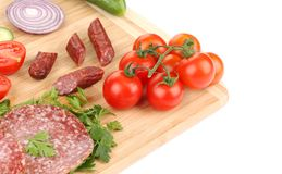 Sausage salami and vegetables on wooden platter. Royalty Free Stock Photo
