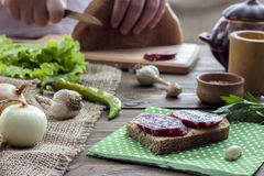 A sausage sandwich. Sandwich with sausage and herbs on a wooden table Stock Photo