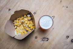 Sausage and sauerkraut on french fries with a beer. Sausage and sauerkraut on a bed of french fries chips with a beer Stock Photos