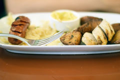 Sausage, sauerkraut, and mustard on a plate Royalty Free Stock Photography