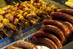 Sausage and skewers on a grill Stock Photos