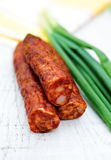 Sausage. Smoked sausage and spring onion on wooden background Stock Photography