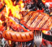 Sausage and steak on a fork. Royalty Free Stock Photography