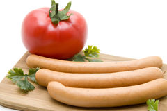 Sausage with tomato. On edge board stock image