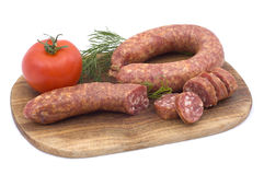 Sausage with tomato and dill. On a wooden hardboard isolated on white Royalty Free Stock Photo