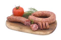 Sausage with tomato and dill. On a wooden hardboard isolated on white Stock Photo