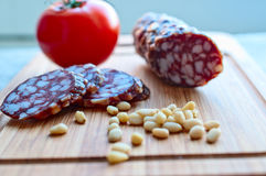Sausage, tomato, pine nuts on  wooden board Stock Photography