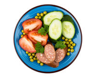 Sausage, tomatoes, cucumbers, green peas and parsley in blue pla Royalty Free Stock Image