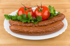 Sausage, tomatoes and greens in dish on board Stock Images