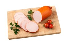 Sausage with tomatoes and herbs on chopping board Royalty Free Stock Photos