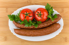 Sausage, tomatoes and parley in dish on bamboo board Stock Photos