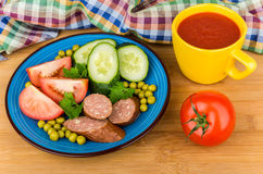 Sausage and vegetables in blue plate, tomato juice in cup Stock Photo