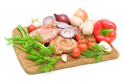 Sausage and vegetables on a cutting board on a white background Royalty Free Stock Images