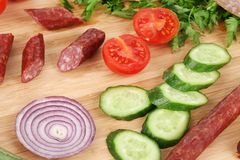 Sausage and vegetables on wooden platter. Royalty Free Stock Image