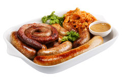 Sausage on a white plate with stewed cabbage and mustard Royalty Free Stock Image