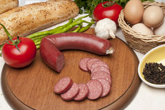 Sausage on wood plate. Bread, tomato, eggs and sausage on wood plate royalty free stock image