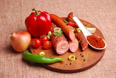 Sausages. Various sausages on wooden plate with vegetables Stock Photos