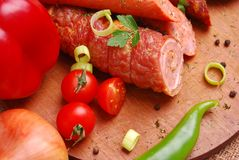 Sausages. Closeup of various sausages on wooden plate with vegetables stock images