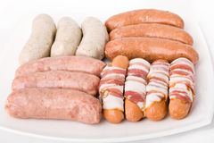 Sausages. Some kind sausages on white plate stock images